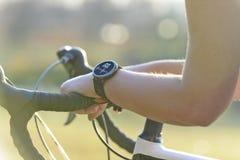 Mulher que monta uma bicicleta e que usa o smartwatch fotos de stock