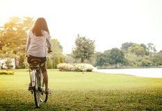 Mulher que monta uma bicicleta em um parque exterior no dia de verão Povos ativos Conceito do estilo de vida Imagens de Stock Royalty Free