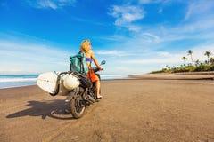 Mulher que monta uma motocicleta com a prancha imagem de stock