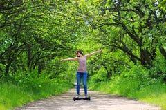 Mulher que monta uma placa elétrica do pairo do 'trotinette' fora -, roda de equilíbrio esperta, 'trotinette' do giroscópio, hyro Foto de Stock