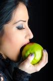 Mulher que morde Apple verde manchado batom Foto de Stock