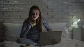 Mulher que morde o hamburguer estragado untasty, tendo a refeição da comida lixo na noite na cama vídeos de arquivo