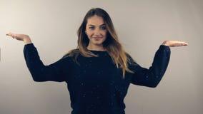Mulher que mostra apontar e apresentar para anunciar, sorriso do sinal da mão alegre video estoque