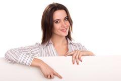 Mulher que mostra e que aponta na bandeira vazia do quadro de avisos Fotos de Stock