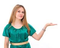 mulher que mostra e que sorri olhando a câmera que explica com mais gest Fotografia de Stock