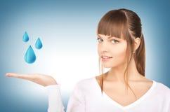 Mulher que mostra gotas da água azul Imagens de Stock Royalty Free