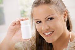 Mulher que mostra o frasco de comprimido Imagem de Stock Royalty Free