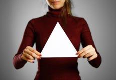 Mulher que mostra o Livro Branco triangular vazio Apresentação do folheto Fotos de Stock Royalty Free