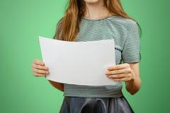 Mulher que mostra o papel A4 grande branco vazio Apresentação do folheto PA Foto de Stock Royalty Free