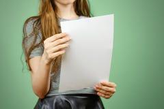 Mulher que mostra o papel A4 grande branco vazio Apresentação do folheto PA Imagem de Stock Royalty Free