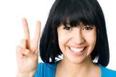 Mulher que mostra o sinal da mão da vitória Fotografia de Stock