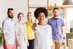 Mulher que mostra os polegares acima sobre a equipe criativa do escritório Imagem de Stock
