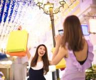 Mulher que mostra sacos de compras na rua da cidade Foto de Stock