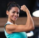 Mulher que mostra seu bíceps no gym foto de stock