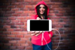 Mulher que mostra a tela vazia do smartphone Fotos de Stock Royalty Free