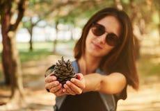 Mulher que mostra um cone de abeto Imagem de Stock