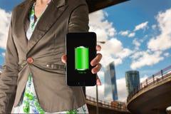 Mulher que mostra um telefone celular com ícone completo verde da bateria Fotografia de Stock Royalty Free
