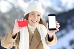 Mulher que mostra uma tela do cartão e do telefone no inverno fotografia de stock
