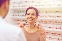 Mulher que mostra vidros ao ótico na loja do sistema ótico foto de stock