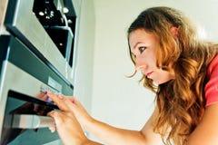 Mulher que move o botão do temporizador no forno Fotos de Stock