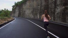 Mulher que movimenta-se na estrada perto do penhasco da rocha video estoque
