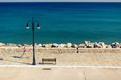Mulher que movimenta-se na rua da cidade no beira-mar Imagens de Stock