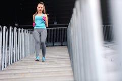 Mulher que movimenta-se para baixo em escadas Os pés malham no estádio, correndo em escadas Conceito da aptidão e da saúde Foto de Stock