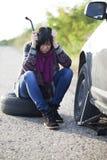 Mulher que muda uma roda em um carro na estrada vazia fotografia de stock