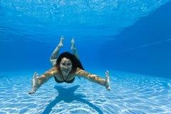 Mulher que nada debaixo d'água em uma associação imagem de stock