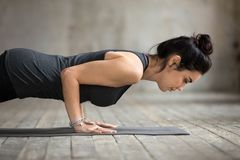 A mulher que nova do iogue fazer empurra levanta ou a imprensa levanta imagem de stock