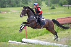 A mulher que o eventer no cavalo está supera a vala aberta Fotos de Stock Royalty Free