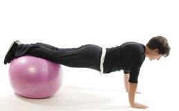 a mulher que o exercício empurra levanta a esfera do treinamento do núcleo Imagens de Stock Royalty Free