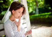 Mulher que obtém chocada na mensagem recebida no telefone Imagens de Stock