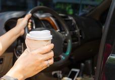 Mulher que obtém em um carro com um copo afastado do café quente foto de stock