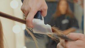 Mulher que obtém o cabelo de lustro pelo cabeleireiro no salão de beleza, close-up filme