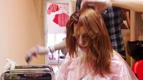 Mulher que obtém o corte de cabelo e colorir