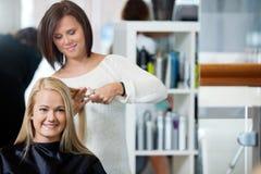 Mulher que obtém o corte de cabelo na sala de estar imagens de stock royalty free