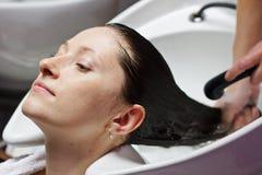 Mulher que obtém uma lavagem do cabelo foto de stock