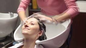 Mulher que obtém uma lavagem do cabelo vídeos de arquivo