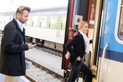 Mulher que obtem no telefone texting do homem do trem Fotografia de Stock