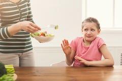 Mulher que oferece lhe a recusa da salada mas da menina da filha imagem de stock royalty free