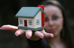 Mulher que oferece uma casa fotografia de stock royalty free