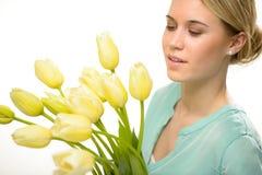 Mulher que olha abaixo das flores amarelas da mola da tulipa Fotos de Stock