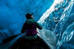 Mulher que olha acima da canoa dentro da caverna de gelo em Alaska imagens de stock royalty free