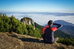 Mulher que olha ao horizonte nas montanhas Fotografia de Stock