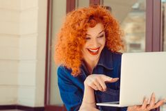 Mulher que olha apontando com o dedo em seu computador foto de stock