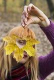 A mulher que olha através da folha com coração deu forma ao furo Fotos de Stock Royalty Free