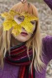 A mulher que olha através da folha do outono com coração deu forma ao furo Imagens de Stock