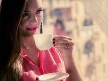 Mulher que olha através da janela, café bebendo de relaxamento Foto de Stock