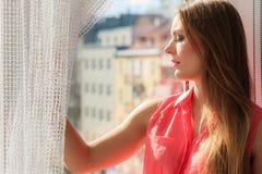 Mulher que olha através da janela, relaxando fotos de stock royalty free